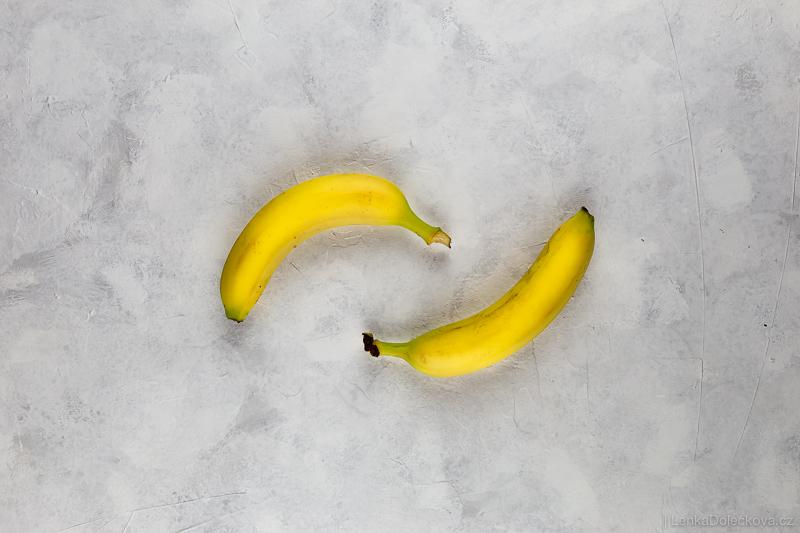 Banány na bílo-šedém podkladu pro fotografování jídla.