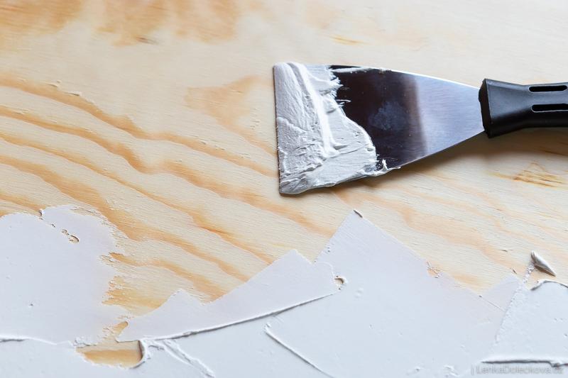 Nanášení akrylového tmelu na překližku při výrobě desky na focení.