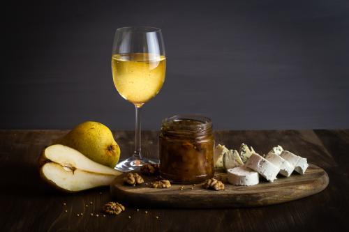 Hruškové chutney se sýrem, hruškami a sklenicí bílého vína.
