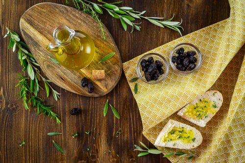 Olivový olej na dřevěné desce, pohled shora.