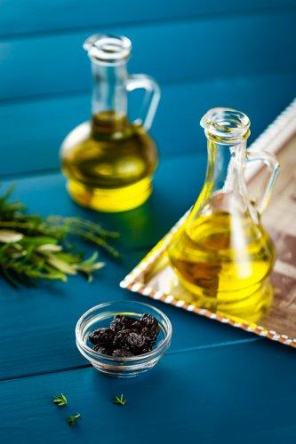 Olivový olej s černými olivami na dřevěné desce.
